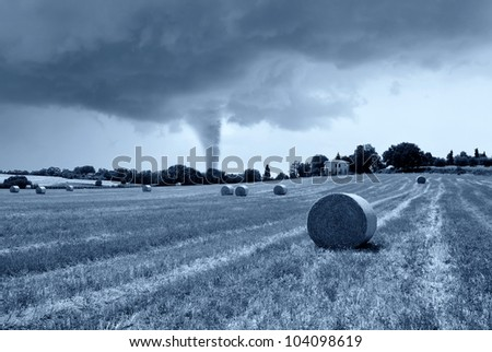 small twister behind the hill - stock photo