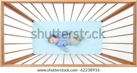 small, two months baby boy lying in a crib (cot) - stock photo