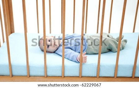 small, two months baby boy lying on backs in a crib (cot) - stock photo