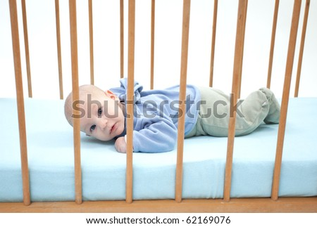 small, two months baby boy lying on stomach in a crib (cot) - stock photo