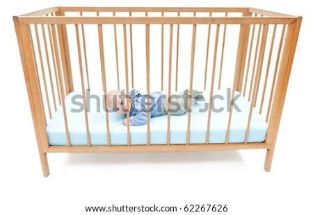 small, two months baby boy, lying on stomach in a crib (cot) - stock photo