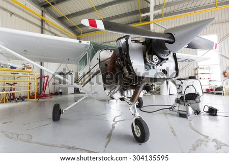 Small two-seated propeller airplane is being repaired in a hangar at the airport. - stock photo