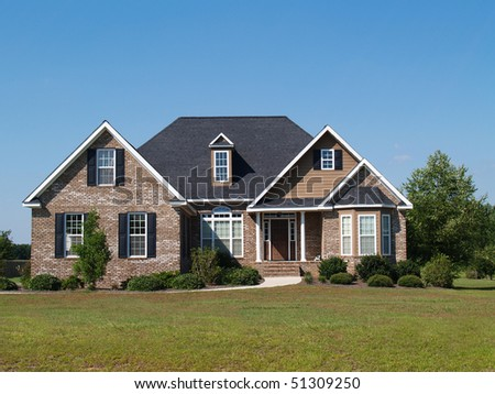 Small two story brick home with porch and a garage on the side containing plenty of copy space, - stock photo