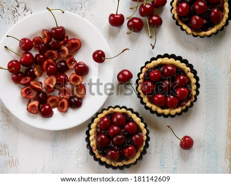 Small uncooked tarts  with fresh cherries on a wooden background with selective focus - stock photo