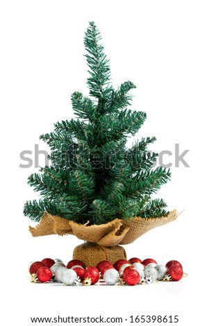 Small undecorated pine with Christmas balls under the tree. Isolated on white.  - stock photo