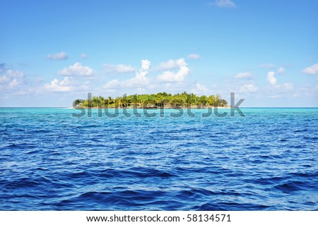 Small uninhabited tropical island in the ocean, Maldives. - stock photo