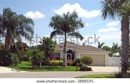 Small upscale house in the tropics with palm trees. - stock photo