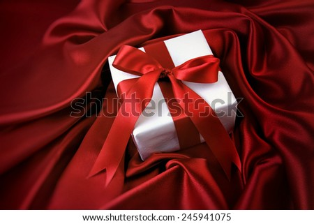 Small valentine gift on red satin - stock photo