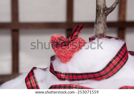 Small valentine's heart with checkered ribbon lying on wedding - stock photo