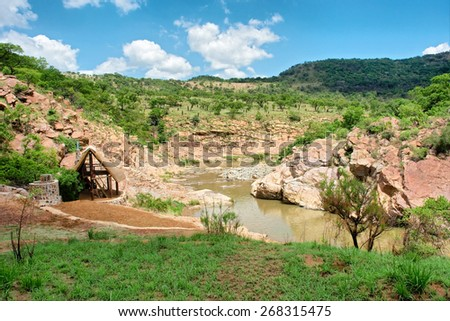 Small valley with mountain river and hut. Shot in Natal province, South Africa.  - stock photo