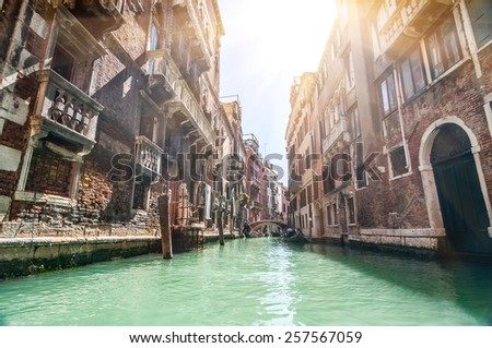 Small venetian canal and old brick walls with vintage traditional balconies. Venice, Italy. - stock photo