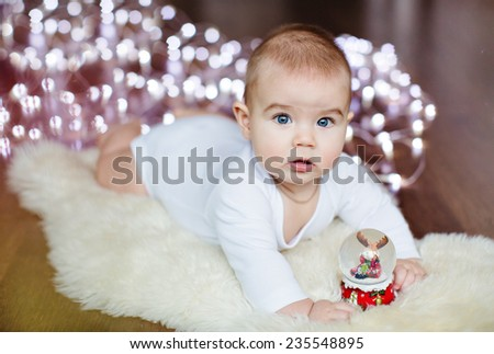 Small very cute baby lying on the floor on the background lights near the Christmas ball - stock photo