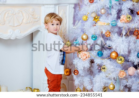 Small very cute blond boy hanging toys on a white Christmas tree - stock photo