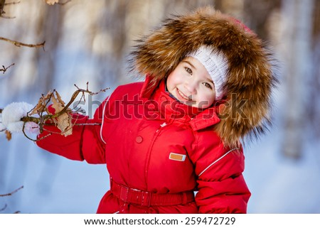 Small very cute girl in a red suit with fur hood standing near a tree in winter forest background and smiles - stock photo