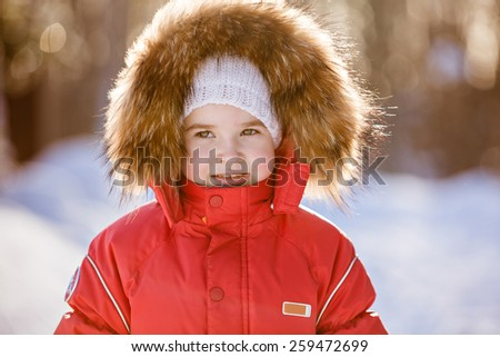 Small very cute girl in a red suit with fur hood winter on the background of snowy sunset forest, close up - stock photo