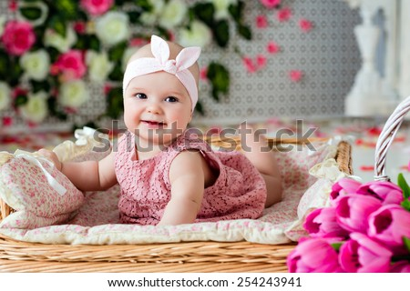 Small very cute wide-eyed smiling baby girl in a pink dress lying in a wicker basket about pink tulips - stock photo
