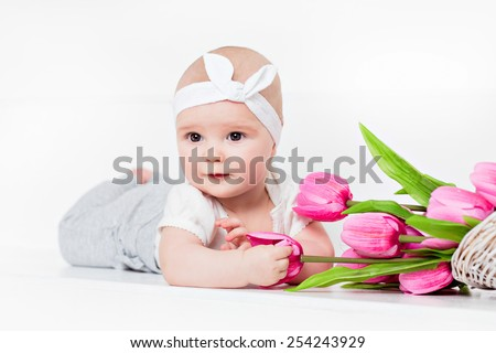 Small very cute wide-eyed smiling baby girl lying on her tummy on a white background in the Studio and keeps handles tulips - stock photo