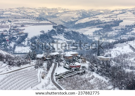 Small village and narrow rural road on  the hills covered with snow in Piedmont, Northern Italy. - stock photo