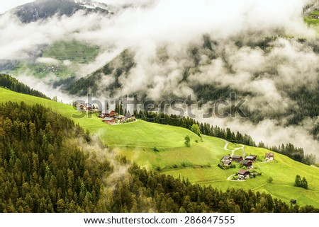 Small village in Dolomite of Italy in the mist  - stock photo
