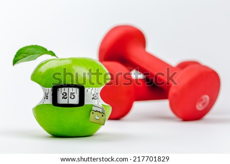 Small waist green apple with dumbbells - stock photo
