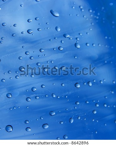 Small water droplets on a transparent blue surface