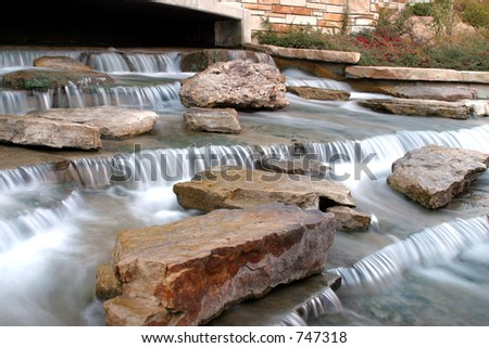 Small water fall at entrance to river walk park. - stock photo
