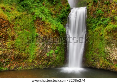 Small water falls dropping into lagoon surrounded with green plants and out to a stream - stock photo