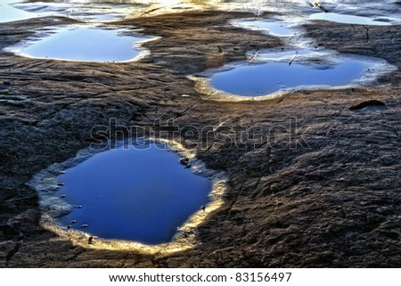 Small water puddles receiving the last kisses from the setting sun - stock photo