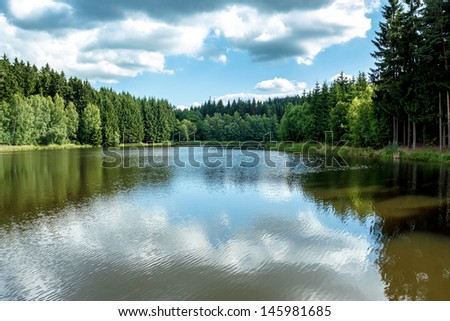 small water water reservoir with blue sky - stock photo