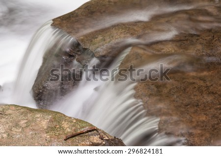 Small waterfall along a swiftly running stream. - stock photo
