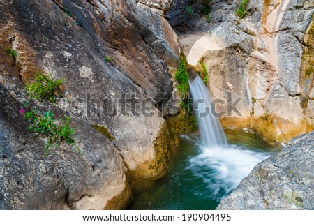 Small waterfall and pond deep in rain forest, shot in long exposure