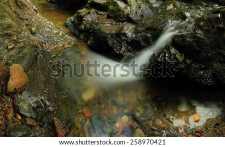 Small waterfall at spring creek with a stone trough