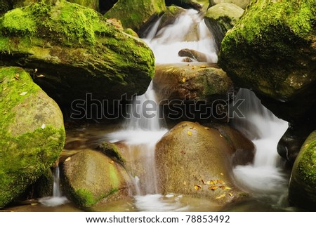 small waterfall between the stones - stock photo