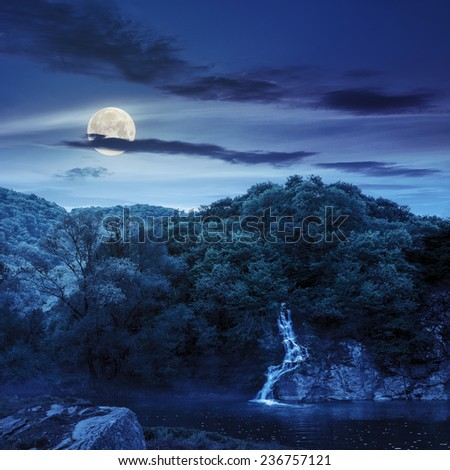small waterfall comes out of a forest on a rocky hill and falls in river with fog at night in full moon light - stock photo