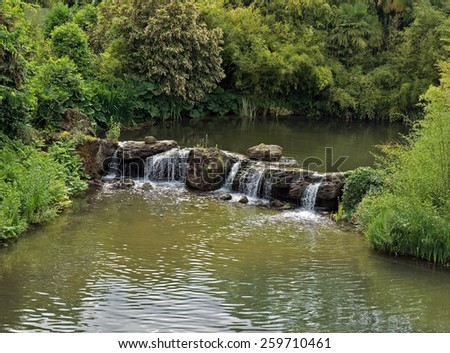 Small waterfall in a lush green forest in France. - stock photo