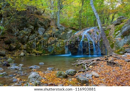 small waterfall in a mountain canyon - stock photo