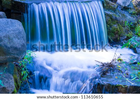 Small Waterfall in shades of blue. - stock photo