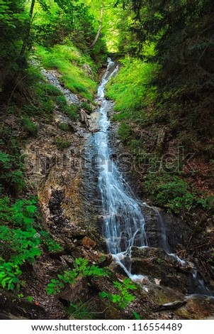 Small waterfall in the dark forest - stock photo