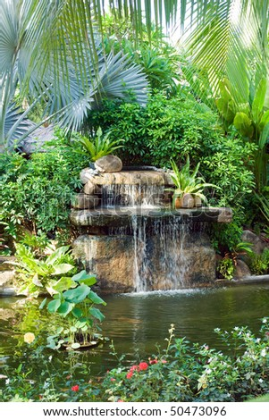 small waterfall in tropical garden - stock photo