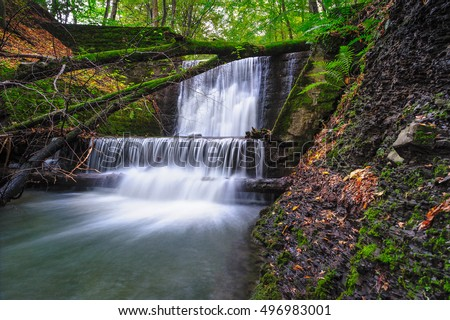 Small waterfall on a river in autumn scenery.