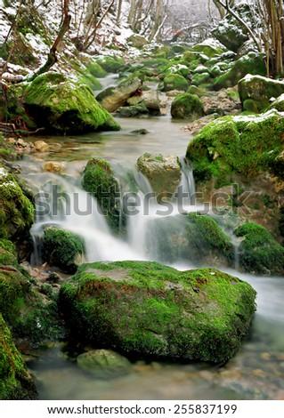 small waterfall on winter mountain stream - stock photo