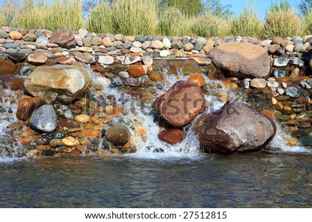 Small waterfall over rocks, in horizontal orientation and desert plants in the background