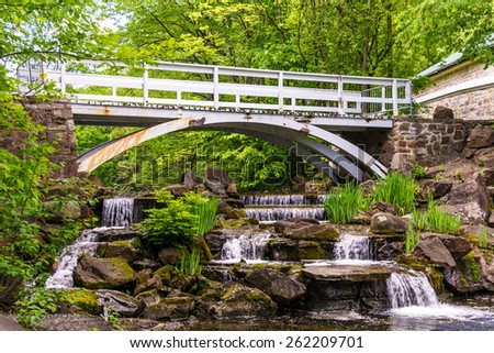 Small waterfall with a footbridge over the falls. - stock photo