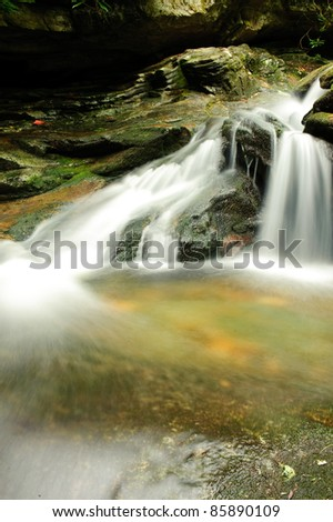 small waterfall with blurred water - stock photo