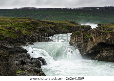 Small waterfalls among cliffs and rocks vocered with moss on a river aboce famous Godafoss waterfall, North Iceland - stock photo
