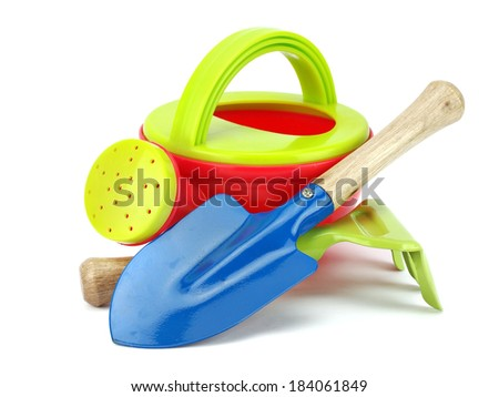 Small watering can, shovel and rake on a white background