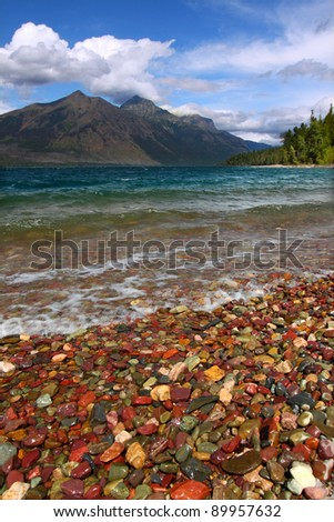 Small waves trickle through bright glacial rocks of Lake McDonald in Glacier National Park.