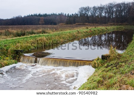 Small weir in a river - stock photo