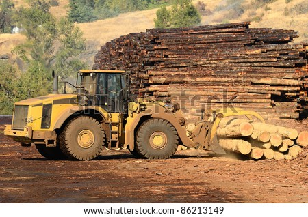 Small wheeled loader moving logs around the log yard at a local sawmill in Oregon - stock photo