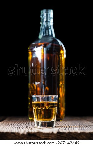 Small Whiskey shot on an old wooden table - stock photo